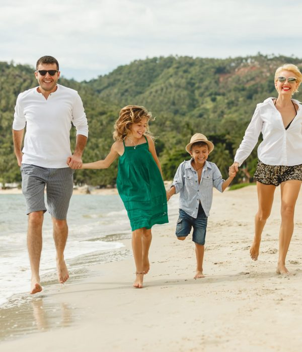 House and Land Package Gladstone - happy family running by beach on tropical island and holding hands
